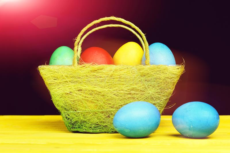 Basket full of painted eggs in red, green, blue, yellow stock photo
