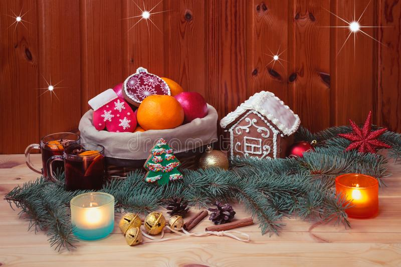 Basket with gingerbread cookies and fruits, little gingerbread house and glasses of mulled wine stock photos