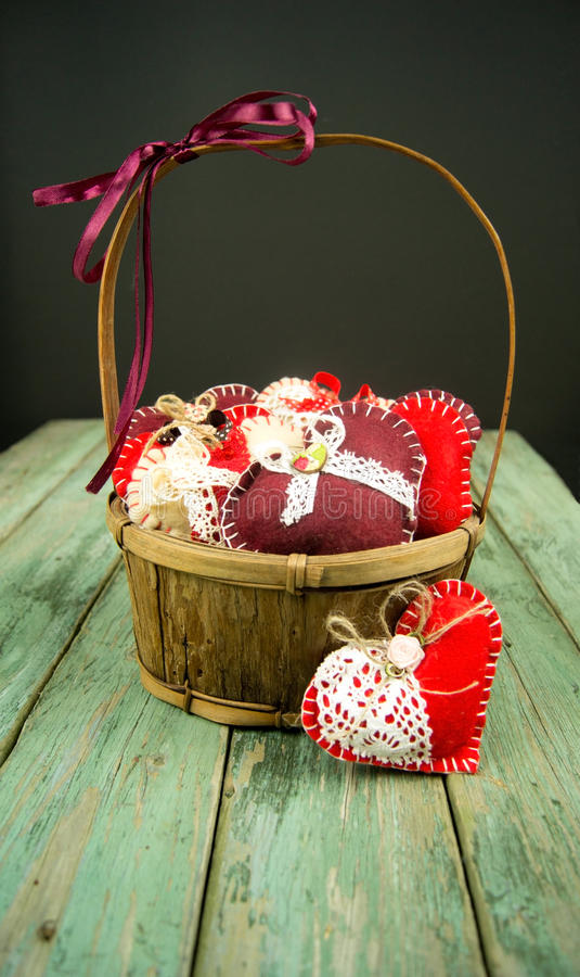 Basket with hearts. On a wooden background royalty free stock photos
