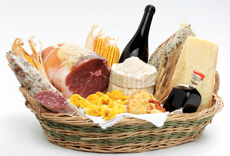 Basket with italian food. It includes Prosciutto di Parma, balsamic vinegar, red wine, mais, salami, Parmigiano Reggiano and tortellini royalty free stock photos