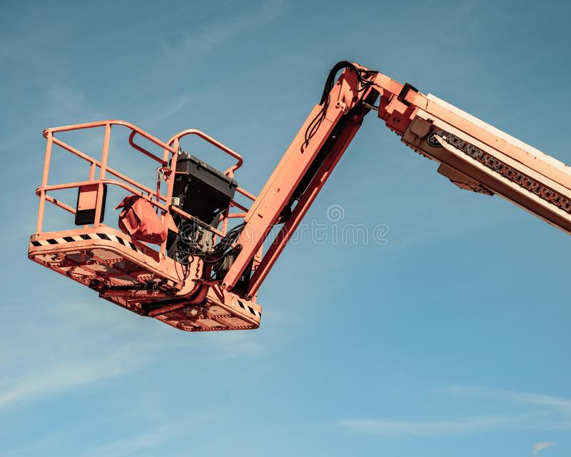 Basket lift on construction site. Basket lift, orange lifting platform on construction site. Industrial machine, work on height equipment concept stock photos