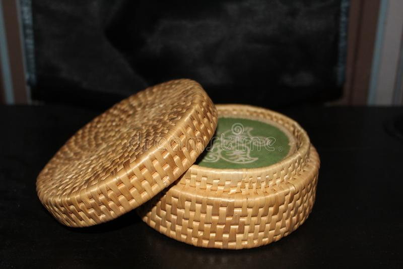 A small cane basket with a green patern. This basket is made of cane , has a green patern on the inside and looks vintage stock image