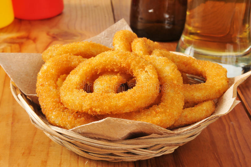 Basket of onion rings. A basket of breaded onion rings with a glass of beer royalty free stock photos