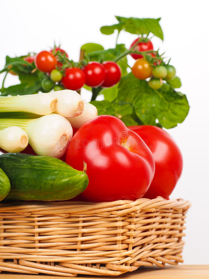 Basket with onion tomatoes and cucumber stock images
