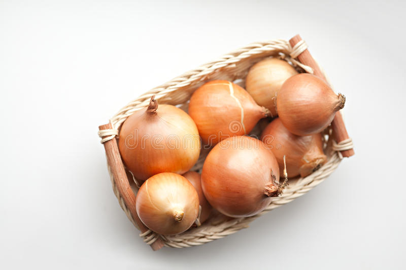 Basket with onoins. Wicker basket with onions. Natural light royalty free stock photo