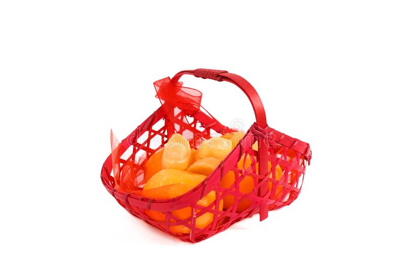 Basket of oranges isolated on a white background. A red basket of oranges and gold ingots made from soap, gift for Chinese New Yea royalty free stock images
