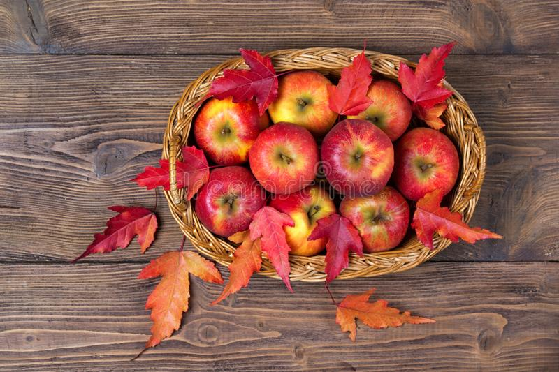 Basket with organic apples and autumn leaves, wooden background stock image
