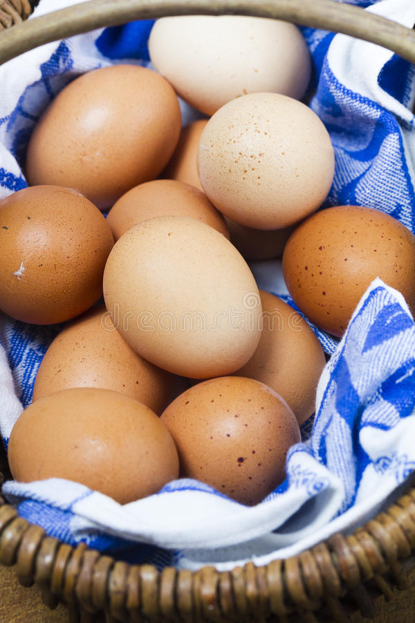 Basket of organic freerange eggs with blue and white cloth. Basket of freerange eggs with blue and white cloth. Medium closeup. Vertical format stock photos