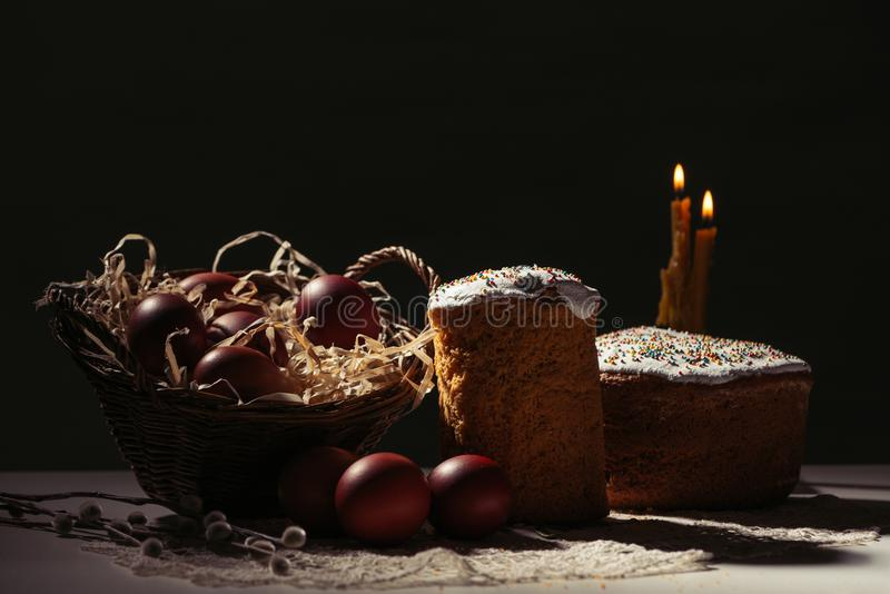Painted eggs in basket, willow twigs and delicious easter cakes. Basket with painted chicken eggs, easter cakes and burning candles on black stock photos