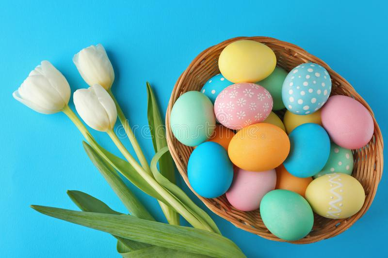 Basket with painted Easter eggs and flowers royalty free stock photography