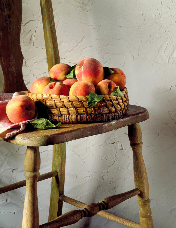 Basket of peaches on chair royalty free stock photography
