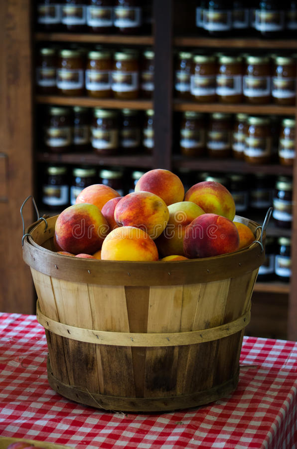 Basket Of Peaches And Jars Of Jelly And Jam Stock Photos