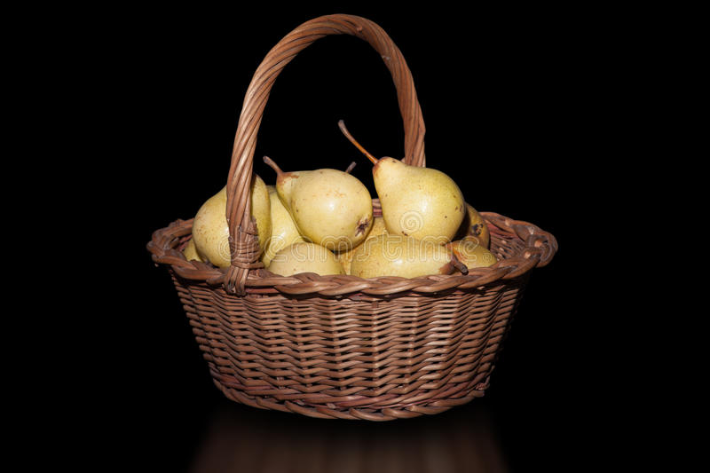Basket with pears on pure black background. stock image