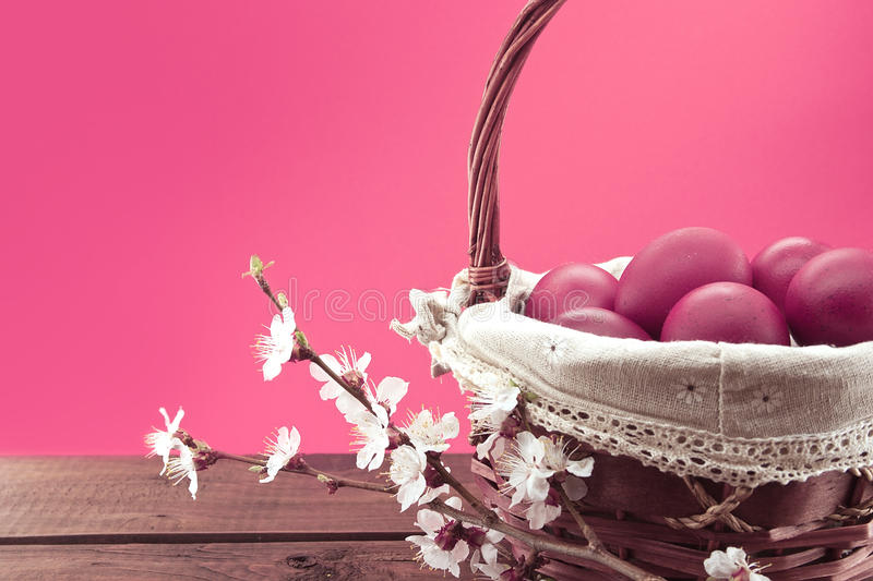 Basket with pink easter eggs on rustic wooden table. royalty free stock image