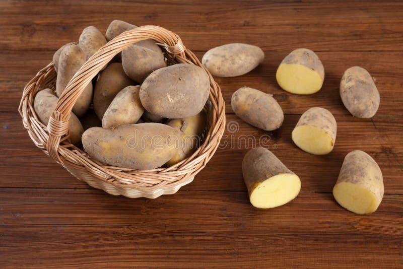 Basket with potatoes, halfed on wood. En background stock photo