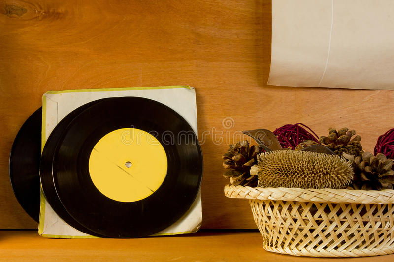 Basket with potpourri and vinyl records. On a wooden background stock photo