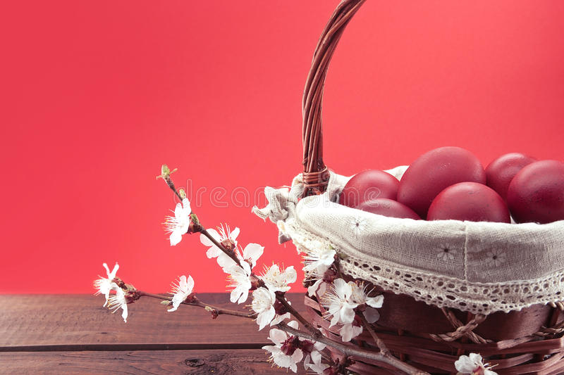 Basket with red easter eggs on rustic wooden table. royalty free stock photos