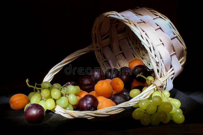 Basket with ripe fresh fruits. Fresh fruits in a basket against a dark background, close-up. Picture for wallpaper, design with stock image