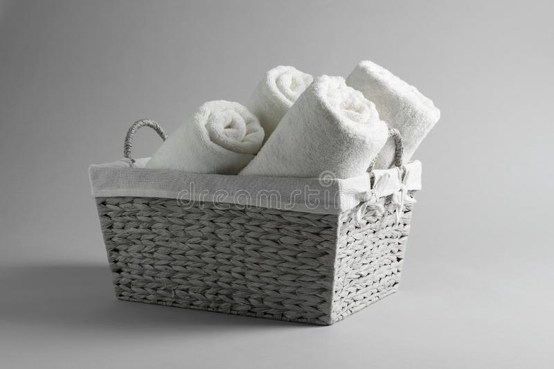 Basket with rolled towels. On light background royalty free stock photography