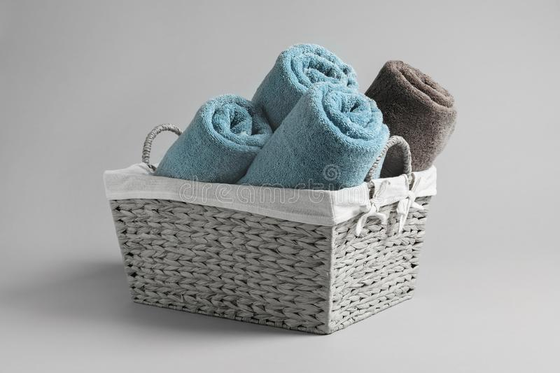 Basket with rolled towels. On light background royalty free stock photo