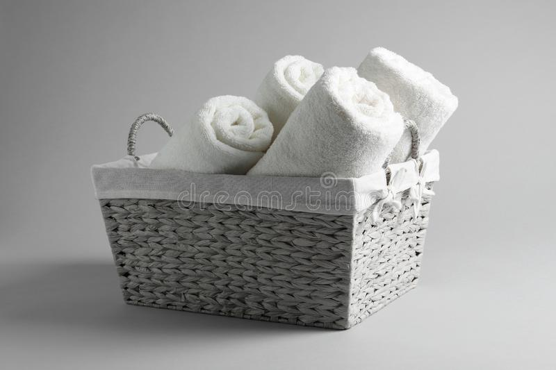 Basket with rolled towels. On light background royalty free stock images