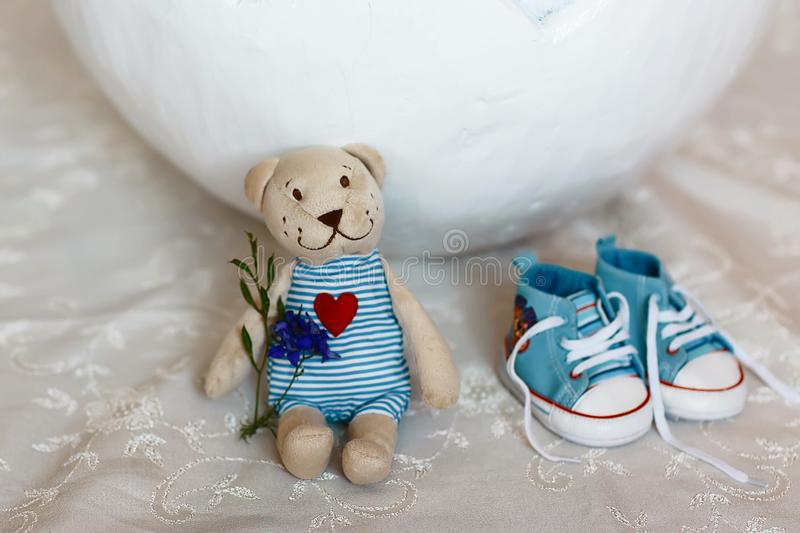 Basket shell of Easter eggs, flat shoes baby boy and a teddy bear with a heart close-up, requisites for a photo session of a newbo. Rn baby stock photos