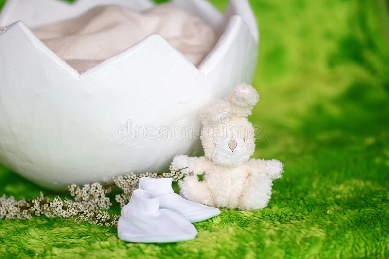 Basket shell of Easter eggs, with a white rabbit, on a green background, requisites for a photo session of a newborn baby royalty free stock photo