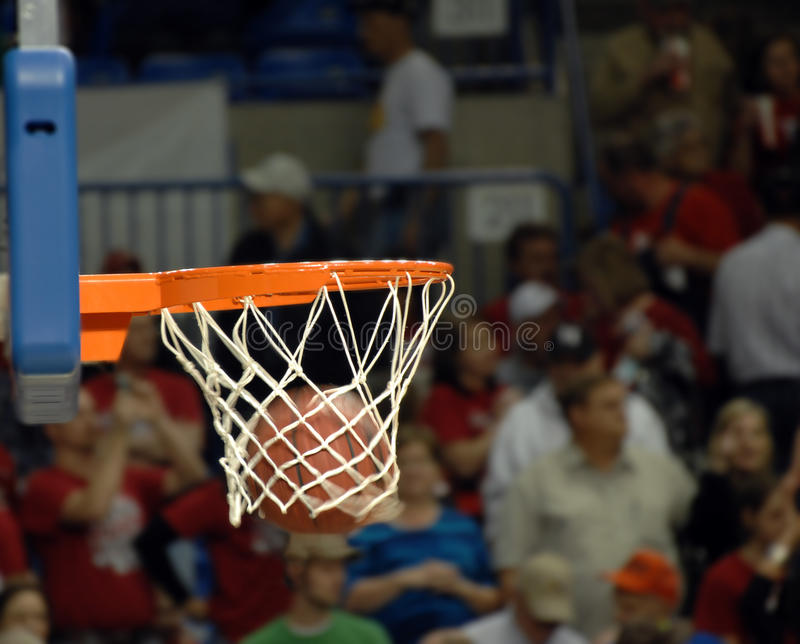 Basket Swoosh. Basketball swooshes through a basketball hoop during a high school basketball game. Crowd shows in the background stock photography
