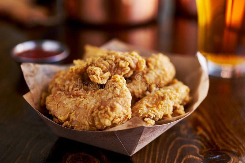 Basket of tasty fried chicken tenders. Shot with selective focus stock image