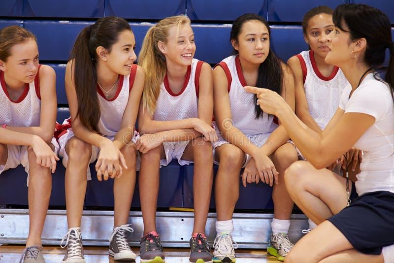 Basket Team Gives Team Talk för lagledareOf Female High skola arkivbild
