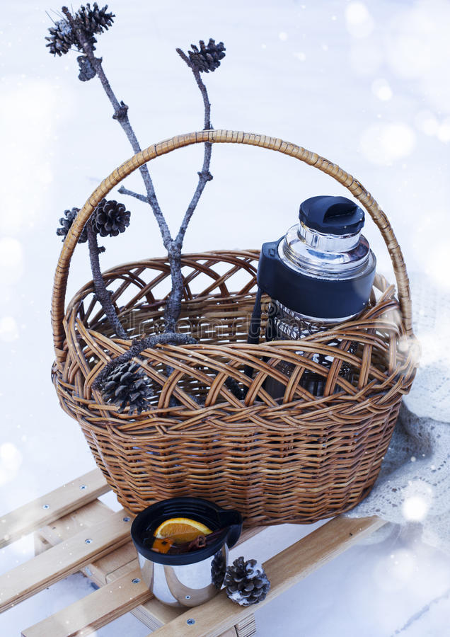 Basket with thermos of mulled wine and knitted blanket on sledge. Basket with thermos of mulled wine, cup and knitted blanket on sledge stock images