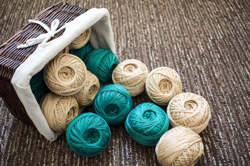 Basket with thread. On the floor is an inverted basket with beige and green knitting yarns royalty free stock images