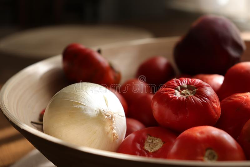 Basket with tomatoes and white onion royalty free stock images