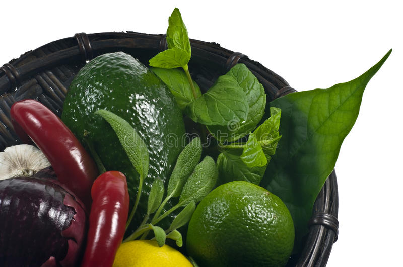 Basket with vegetables. And herbs isolated on white royalty free stock images