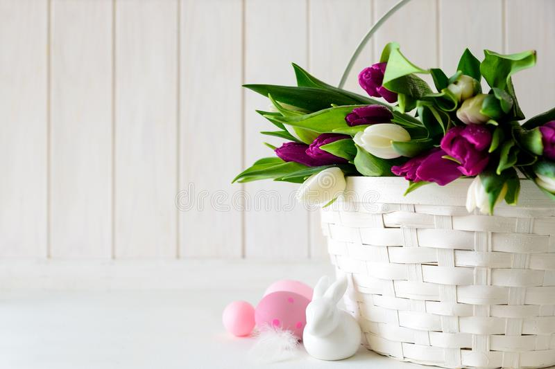 Basket with white and purple tulips, Easter eggs and rabbit on white wooden background. Copy space royalty free stock photos