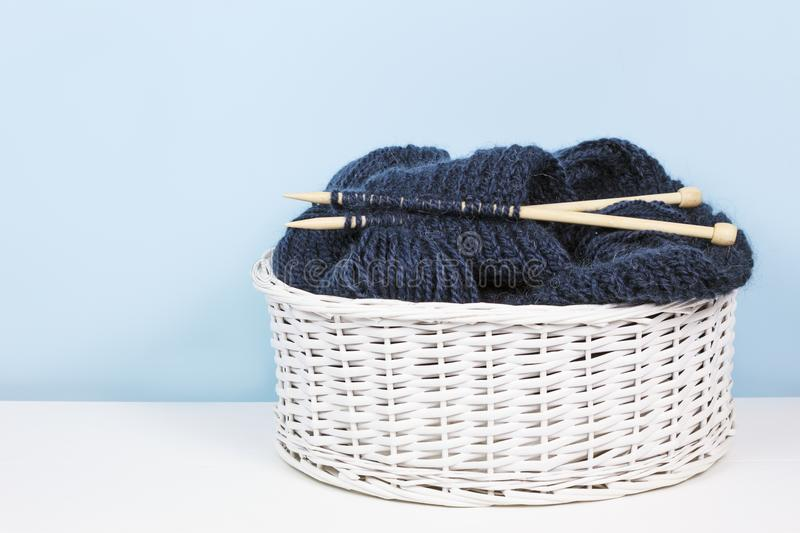 Basket with woolen yarn and knitting needles, balls of thread. stock photo
