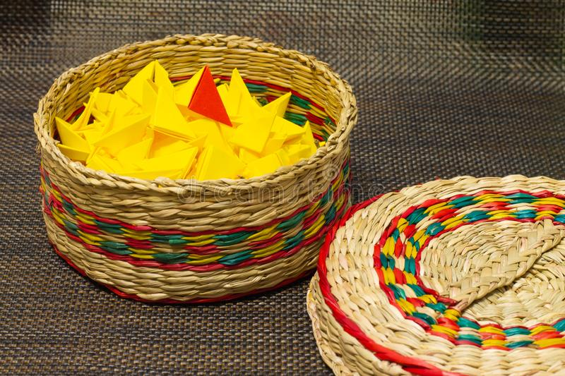 Basket of woven straw with yellow paper stock images