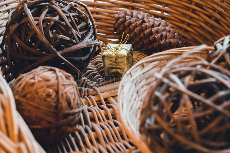 In a basket that is woven from a vine, there are balls that are also woven from a vine and cone of coniferous trees. Between them. Is a small box packed with a royalty free stock images