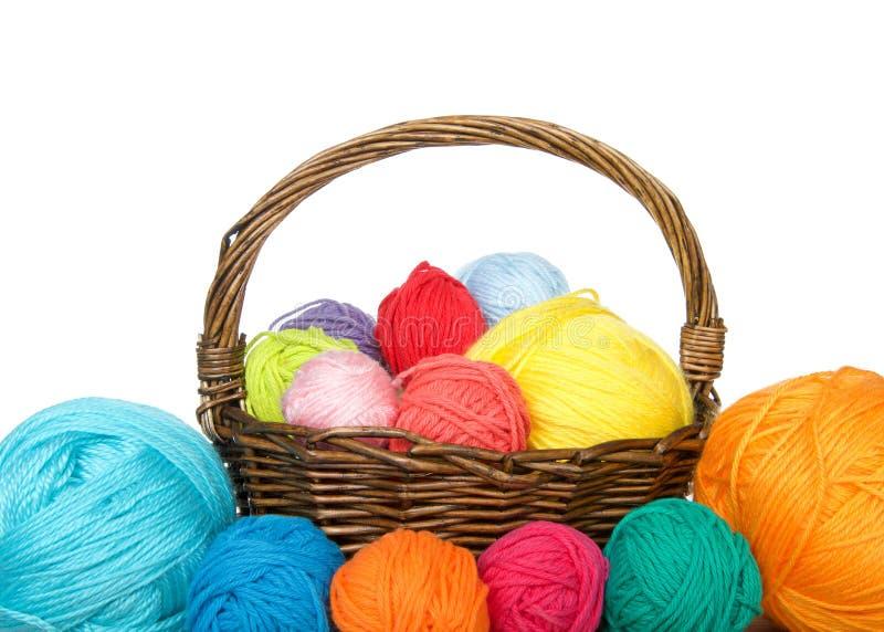 Basket of yarn with balls of yarn surrounding isolated stock photo