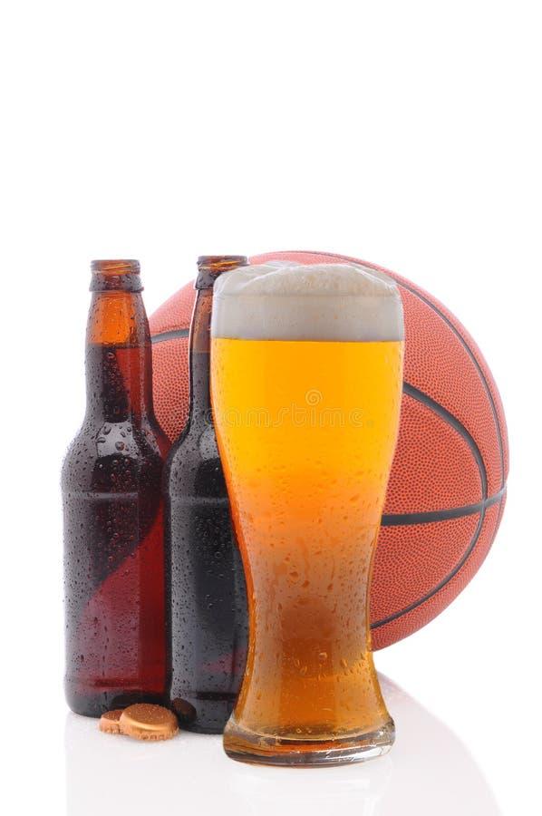 Basketbal en twee bierflessen en Glas stock afbeelding