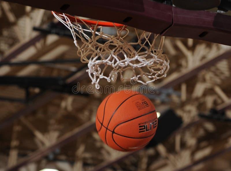 Basketbalbal die door het net gaan stock fotografie