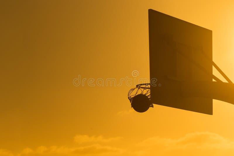 Basketbalhoepel met zon die vanuit een invalshoek glanzen stock afbeelding
