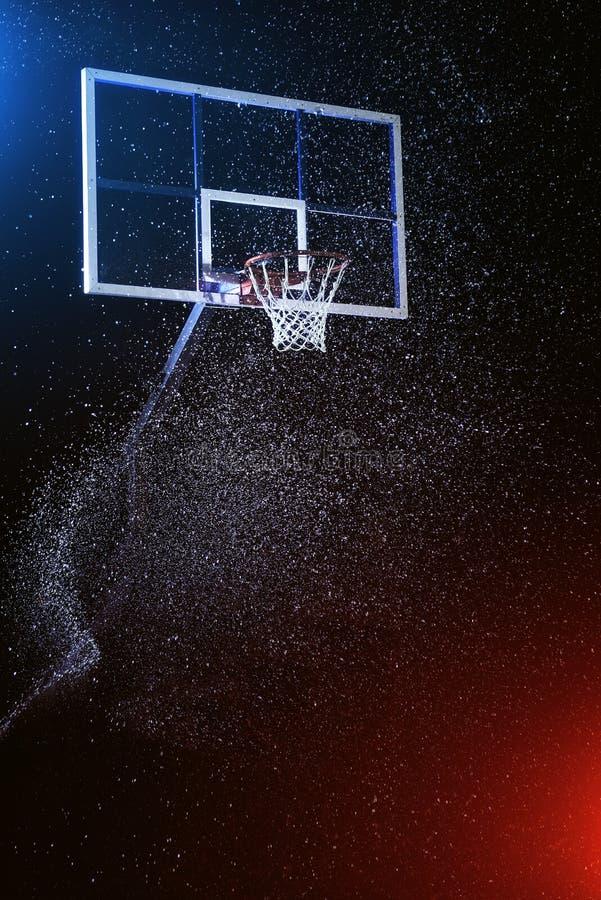 Basketbalhoepel op zwarte Basketbalarena onder regen Verlicht door gemengde kleurenlichten royalty-vrije stock fotografie