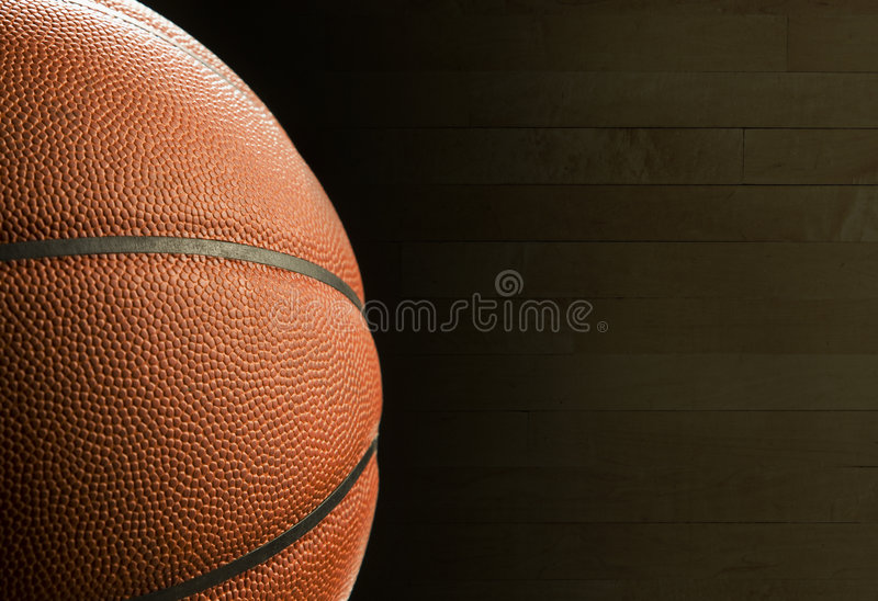 Basketball. A close-up of a basketball with a shaded basketball floor boards in the background stock image