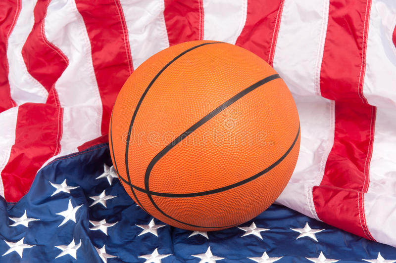 Basketball on American Flag. A basketball on an American flag show a patriotic sport royalty free stock photo