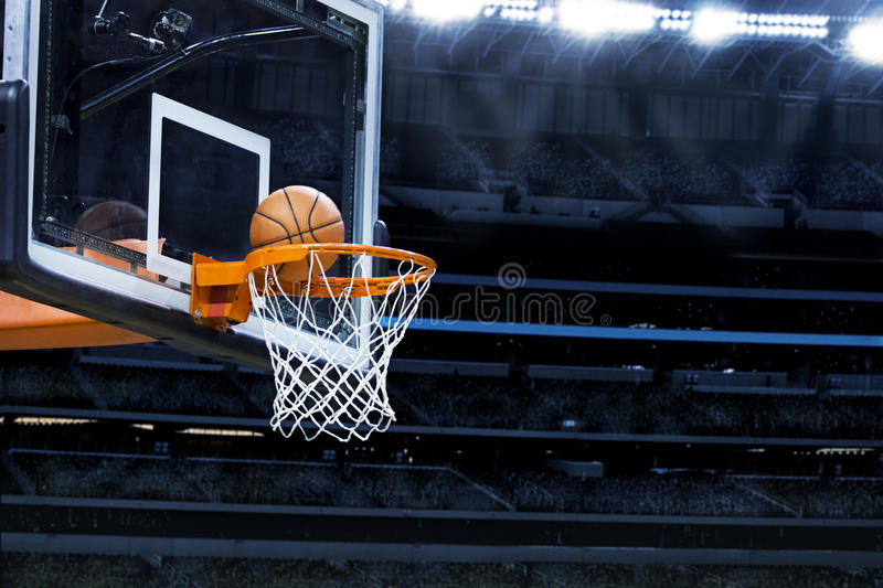Basketball Arena. An action photo of a basketball going through the basket of a live game. In a large professional basketball arena royalty free stock photo