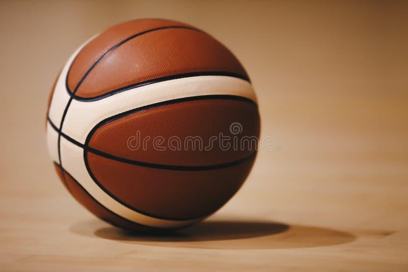 Basketball auf hölzernem Gerichts-Boden-Abschluss oben mit unscharfer Arena im Hintergrund lizenzfreie stockfotografie