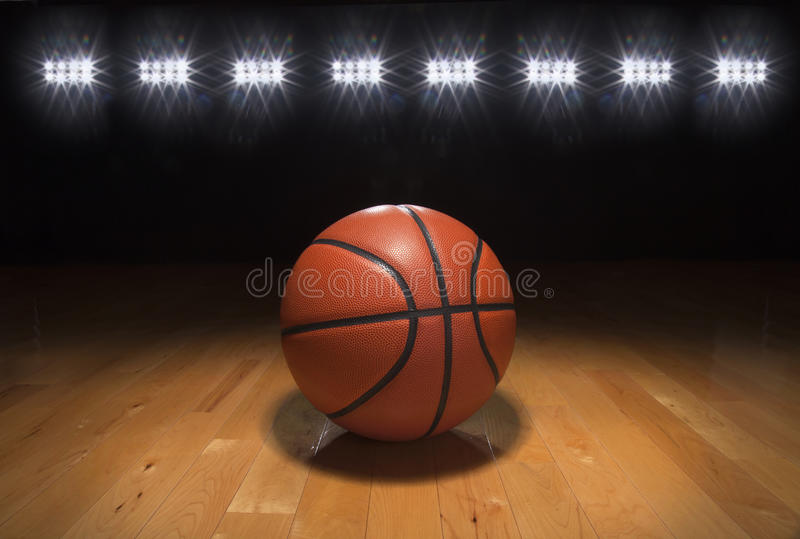 Basketball auf Holzfußboden unter hellen Lichtern stockbild