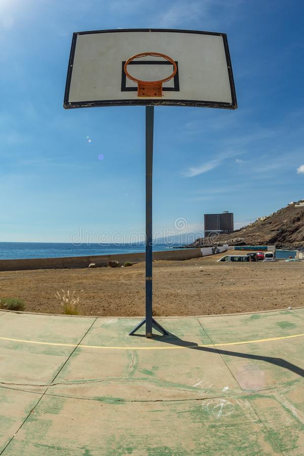 Basketball backboard with basket on the old sports field. Huge Abandoned building in front of the ocean in the far background. stock images