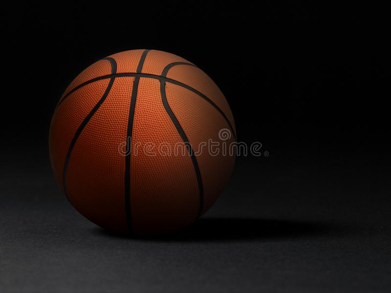 Basketball ball on black background. In the dark room. For design In the media stock images